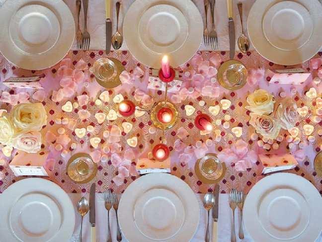 Mesa posta de Jantar romântico com luz de vela, pétalas de rosa e corações espalhados pela mesa