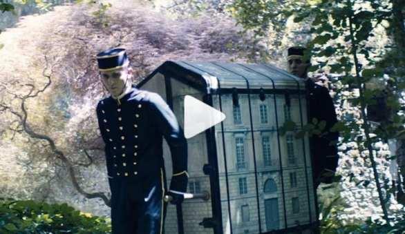 Baú de vestidos em miniatura contidos em um baú de viagem com a emblemática fachada de Paris