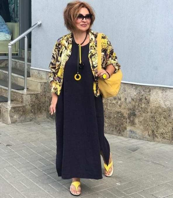 Senhora com look estiloso de vestido preto com casaco estampado e acessórios amarelos - Sou plus Size