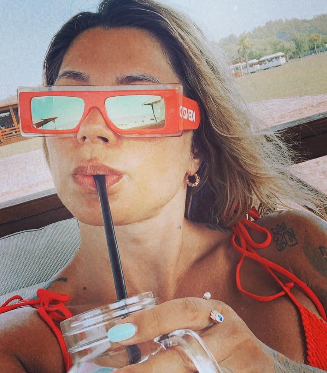 Dani Souza usando óculos de sol vermelho tomando água.