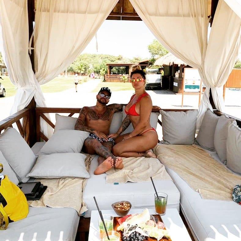 Foto de Dani e seu esposo Dentinho, sentados em sofás de área de piscina.