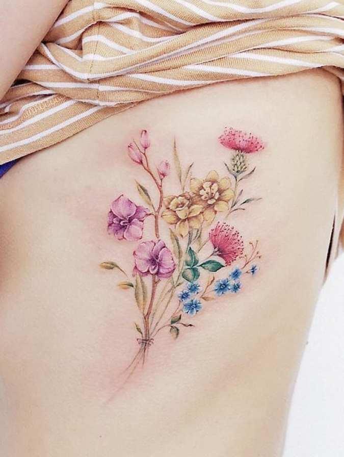 Buquê colorido de flores na lateral do corpo