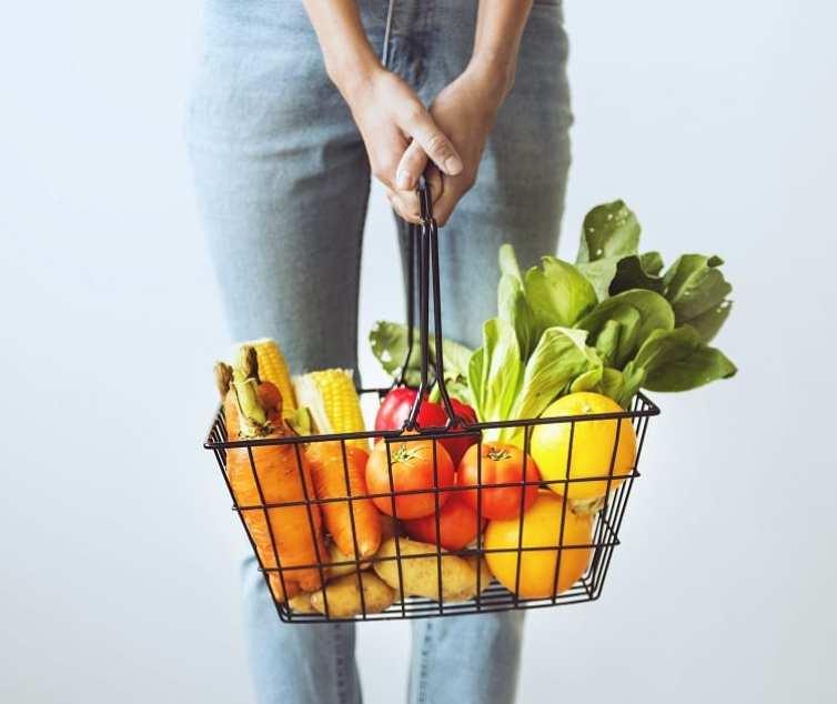 mulher carregando cesta de mercado com frutas, verduras e legumes