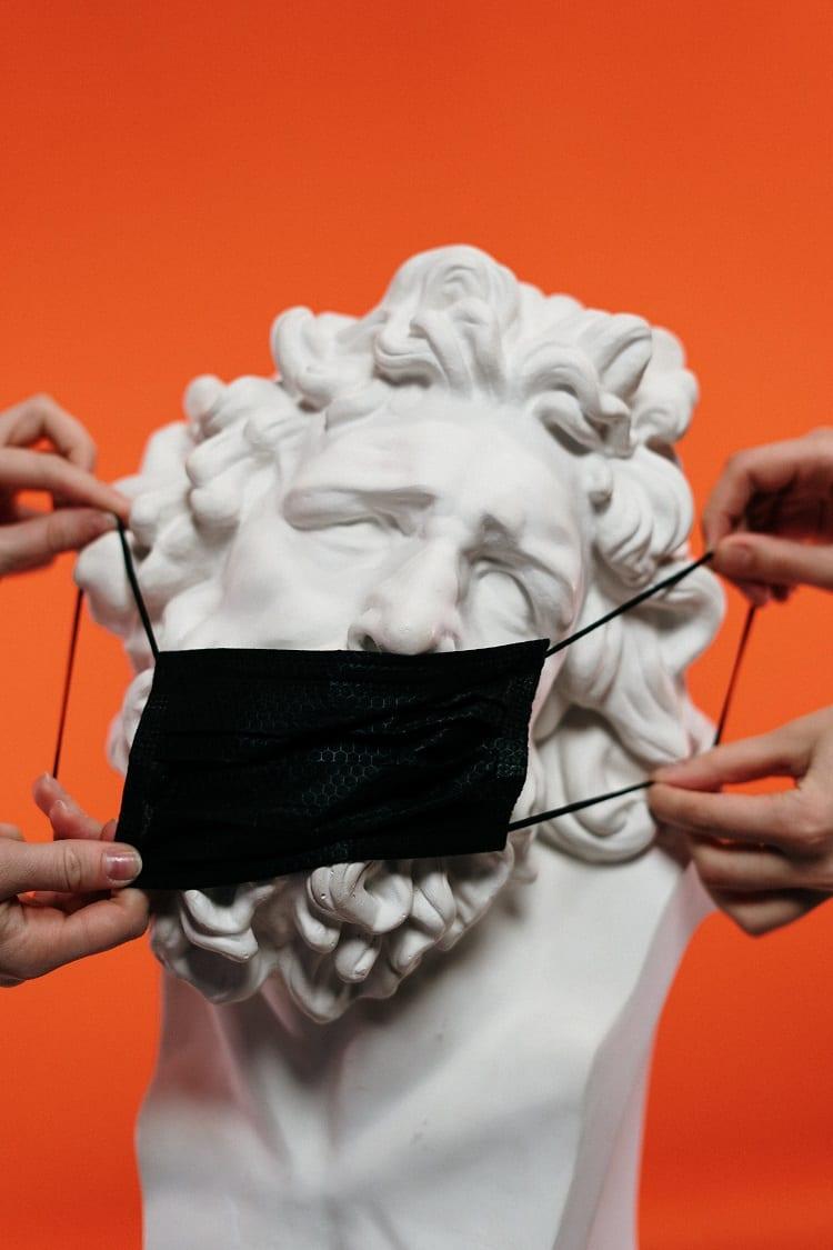 estátua de mármore usando uma máscara preta