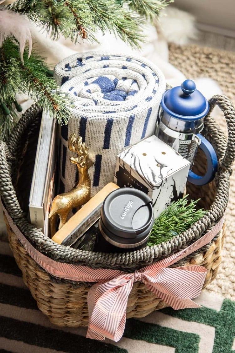 cesta com livro, cafeteira, xícara, vela e manta