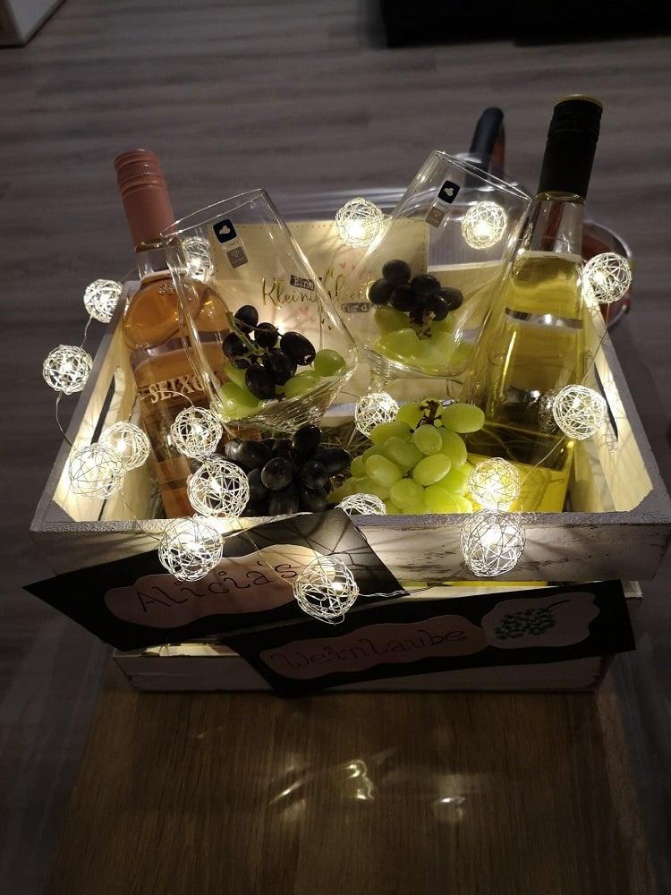 caixa com vinhos, taças, uvas e luzes
