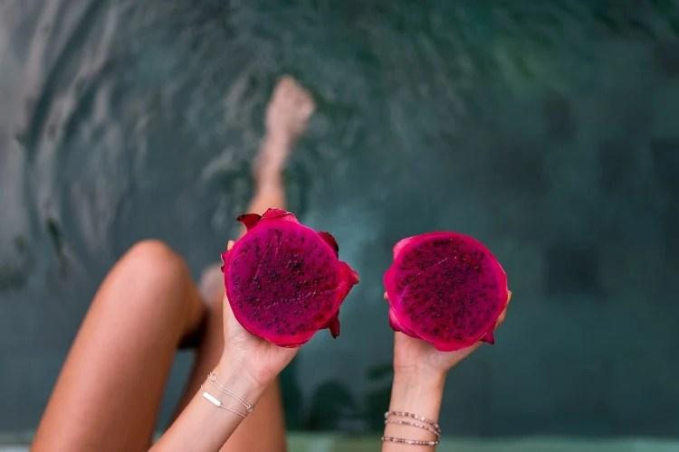 mulher segurando duas metades da pitaya vermelha