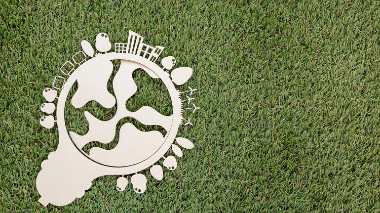 lâmpada em um fundo de gramado verde, simbolizando ideias para um mundo mais sustentável