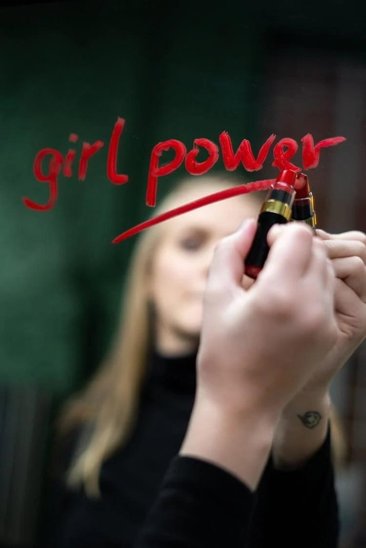 """mulher loira escrevendo """"girl power"""" no espelho com batom vermelho"""