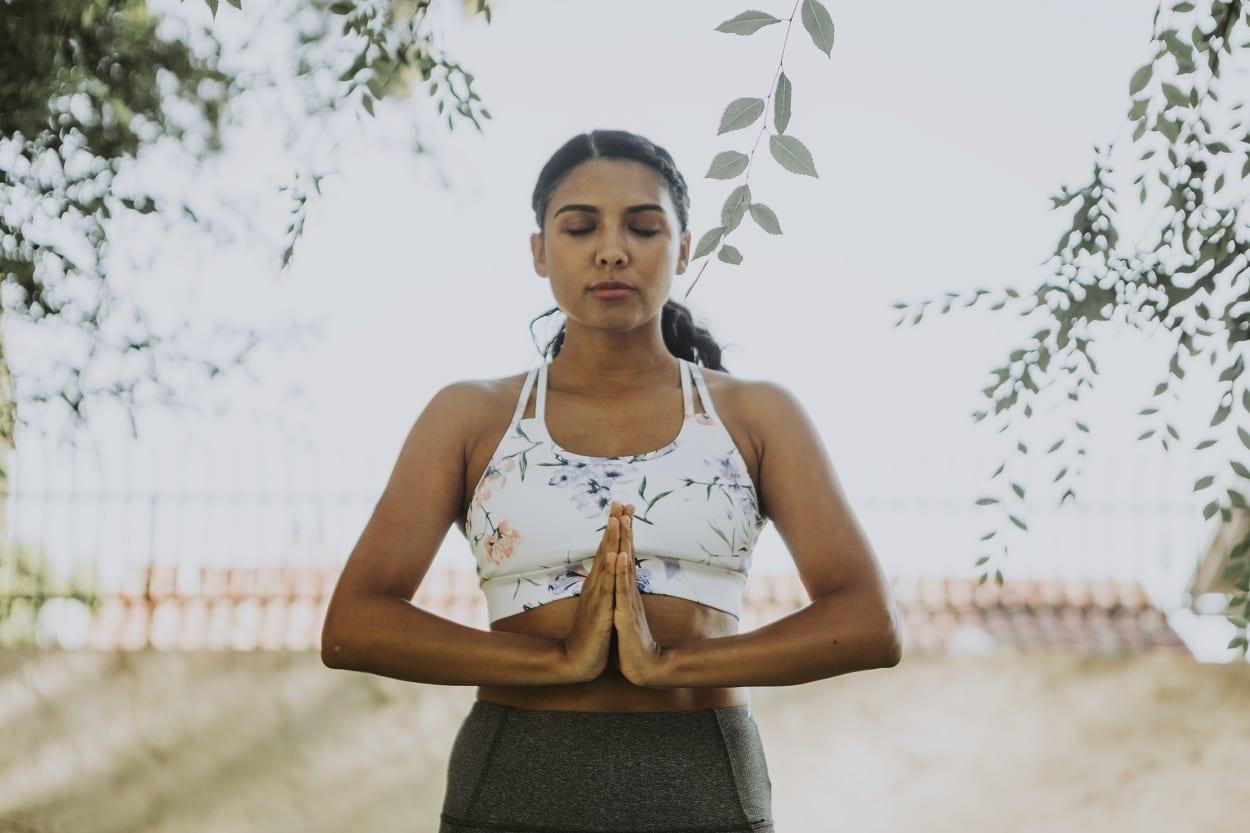 mulher meditando em pé, buscando o equilíbrio, um dos conceitos que define o que é ayurveda