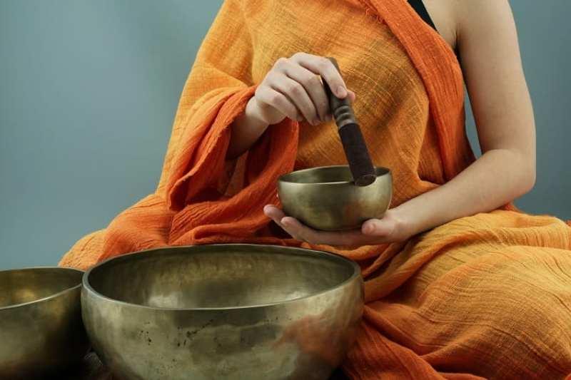 mulher com sinos tibetanos para meditação