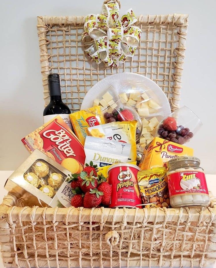 garrafa de vinho, tábua de queijos, taças, aperitivos, morangos e chocolate em uma cesta