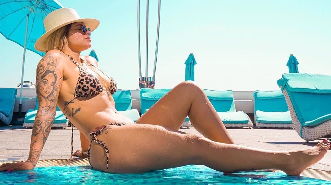 Dani Souza sentada em área de piscina.