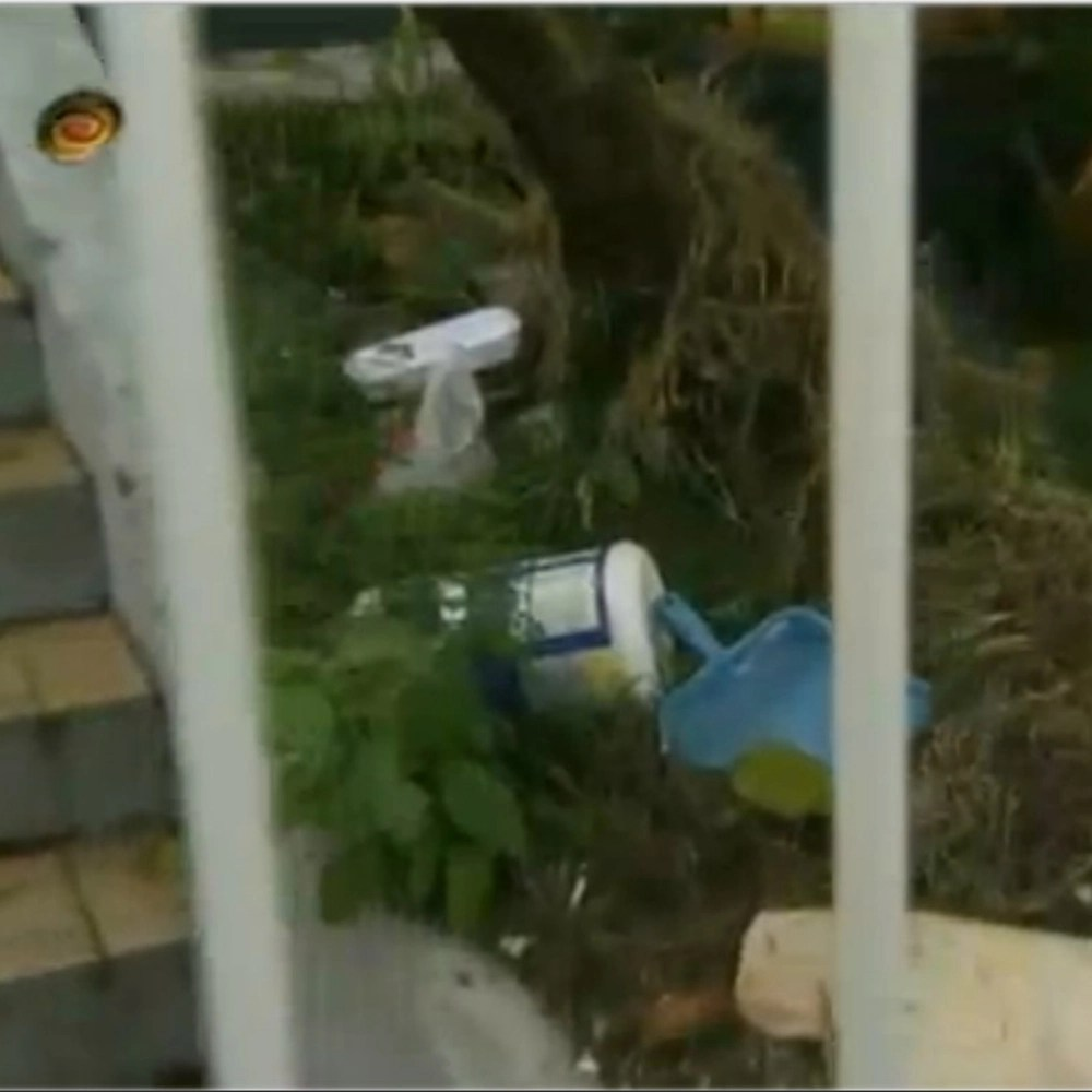 Lixo do lado da escada de entrada da casa