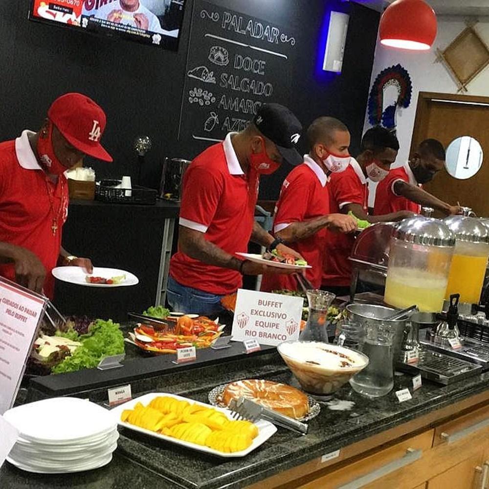 Jogadores fazendo refeição em buffet exclusivo.