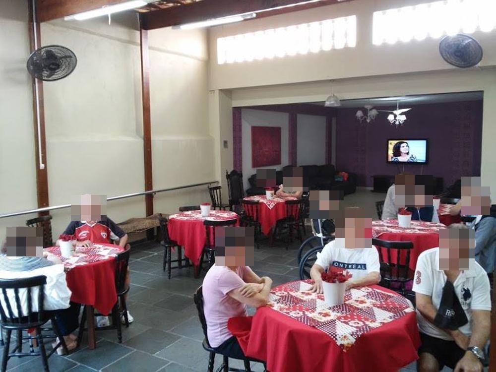 Salão de refeição com mesas de quatro cadeiras.