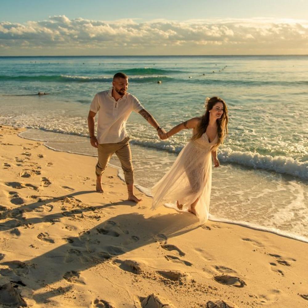 Casal em lua de mel, na praia.