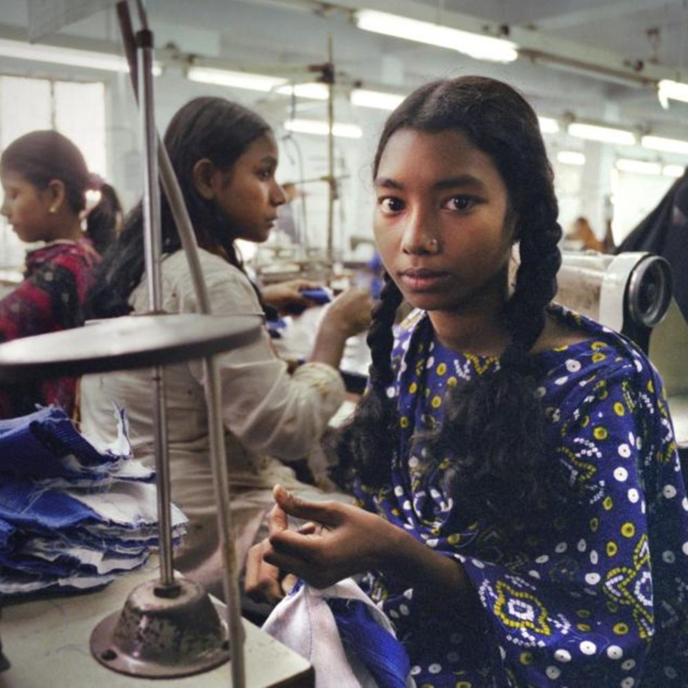 Criança trabalhando em seção de costura.