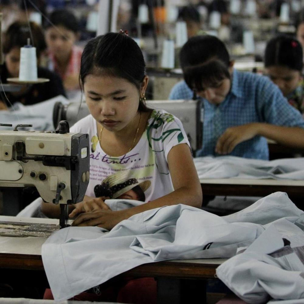 Jovem trabalhando em máquina de costura.