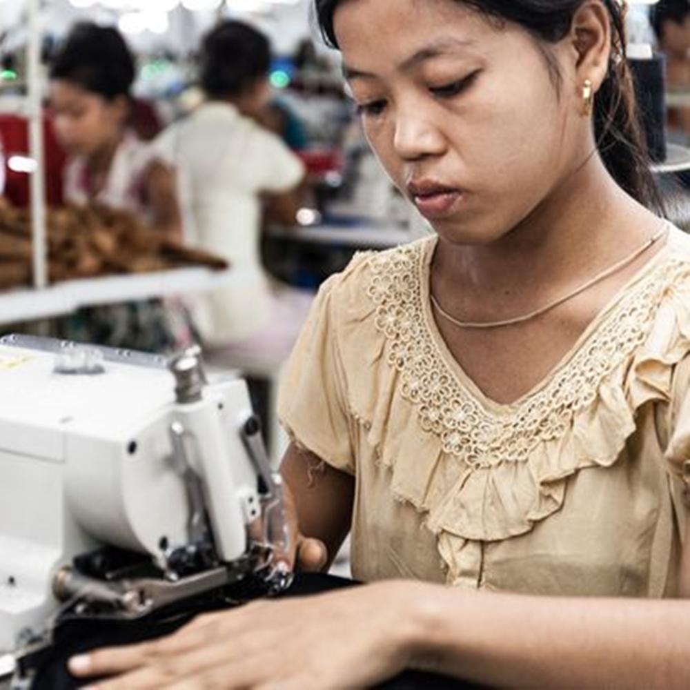 Mulher trabalhando em produção de roupas.