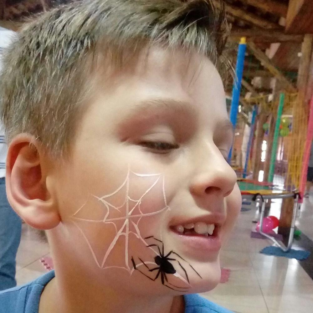 Menino com aranha desenhada no rosto - Halloween em casa.