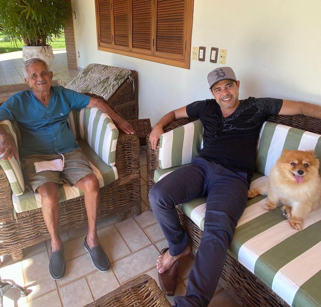 Esposo de Helena e filho em varanda com cachorro.