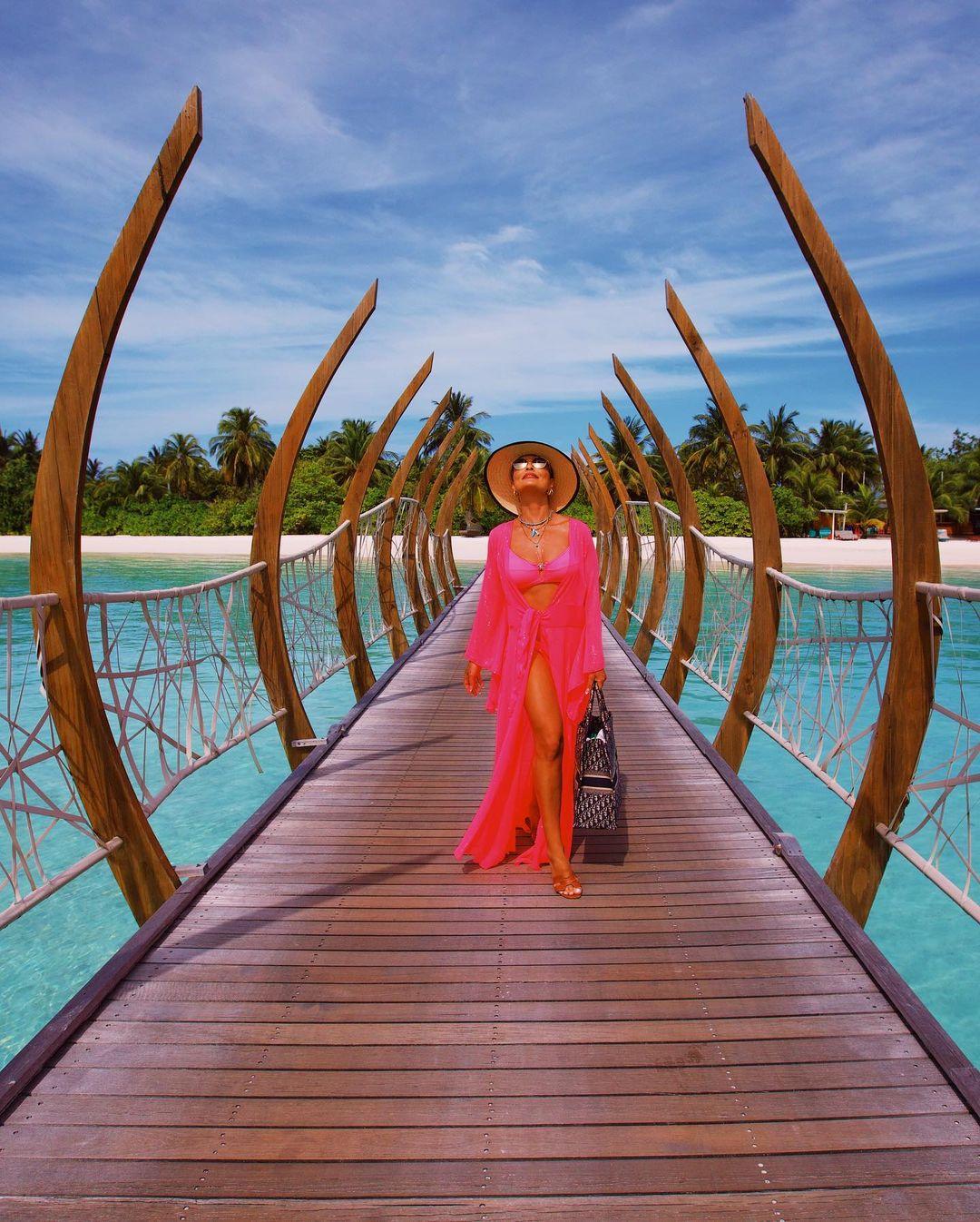 Artista andando em ponte no alto mar das Maldivas.