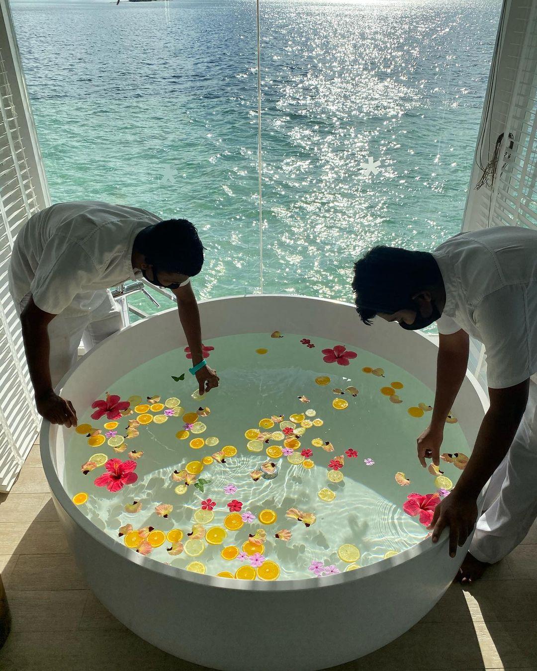 Dois homens organizam frutas na banheira de Juliana Paes.