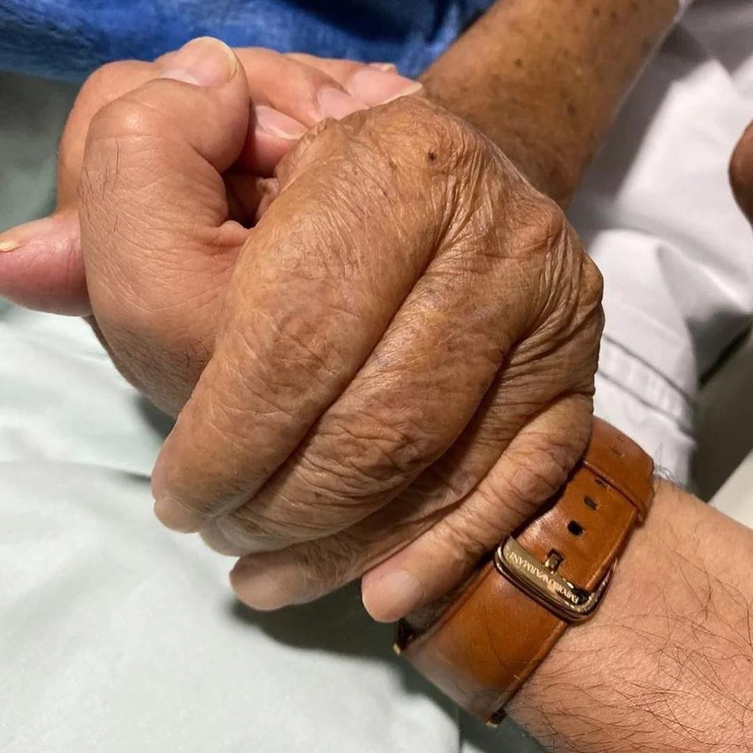 Zezé segura a mão de seu pai em hospital.