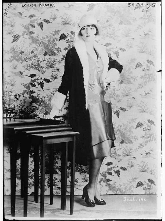 Foto da atriz Louise Brooks posando com um vestido curto e chapéu clochê, por volta de 1929. Look da Moda e Cidadania nos anos 20 e 30.