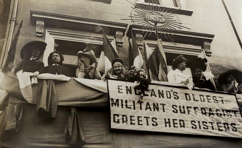 Elizabeth Wolstenholme observa uma processão de mulheres sufragistas em 1911.