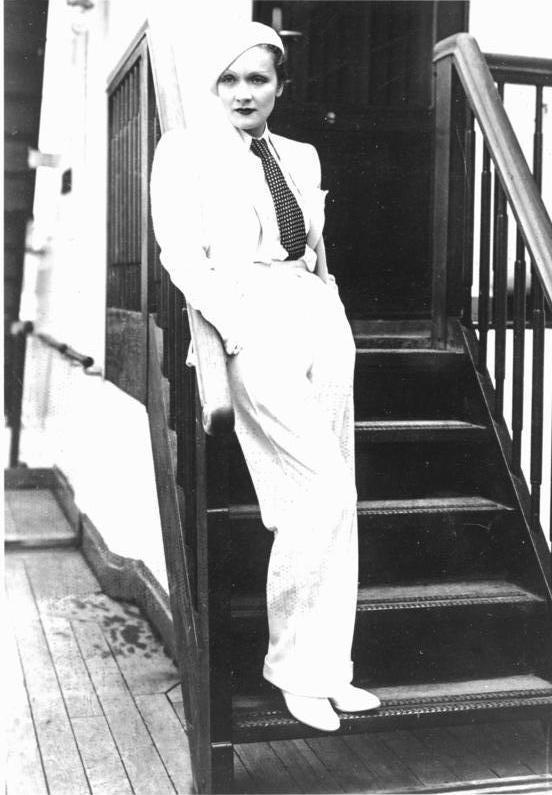A atriz Marlene Dietrich vestida com um terninho branco e fravata, em 1933. Look da Moda e Cidadania nos anos 20 e 30.