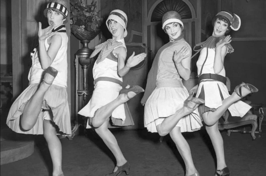 Mulheres dançando nos anos 30, com chapéu clochê e vestidos mais curtos. Look da Moda e Cidadania nos anos 20 e 30.