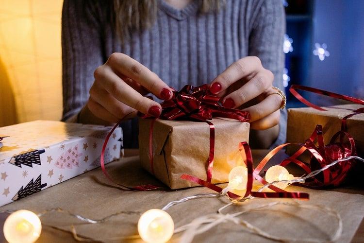 mulher embrulhando presente com um laço vermelho