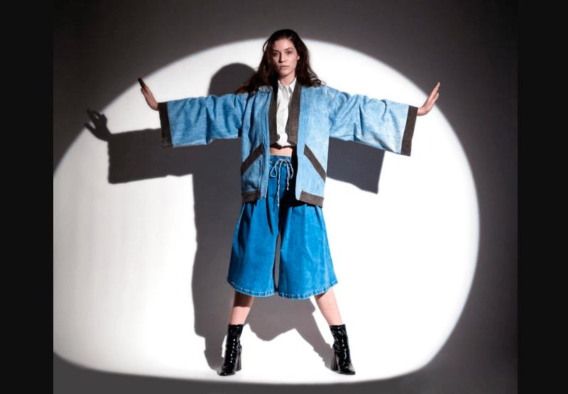 Modelo usa kimono e calça pantalona midi em jeans leve e botas pretas