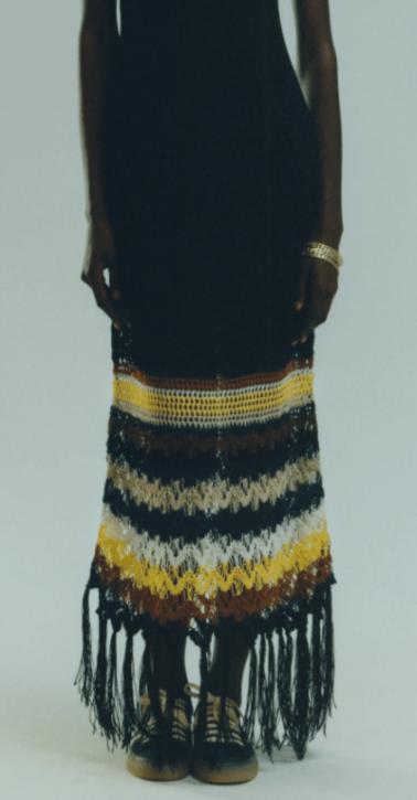 Modelo usa vestido com barra em tricô padrão listrado