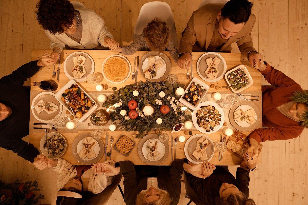família reunida em volta da mesa rezando orações de Ano Novo