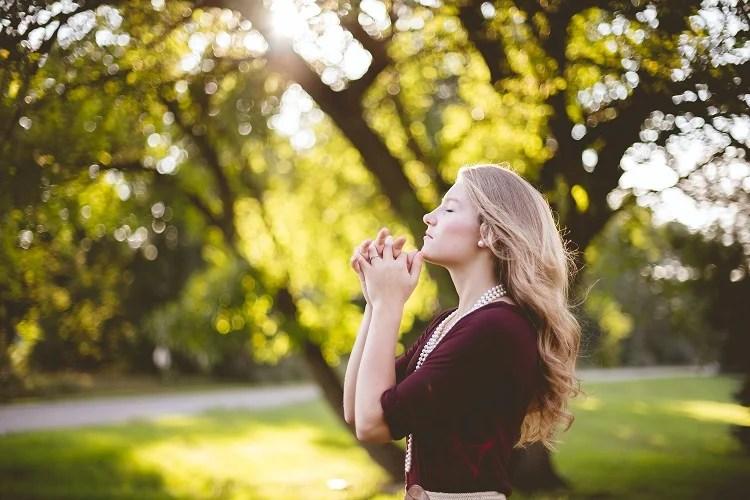 mulher de olhos fechados fazendo orações de Ano Novo