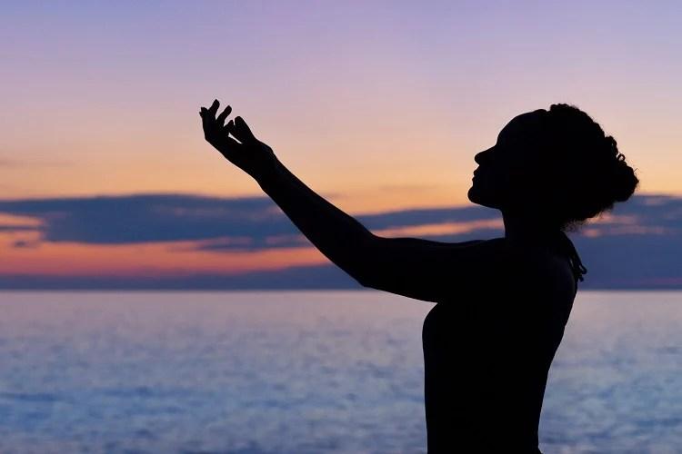 silhueta de mulher pedindo bênção