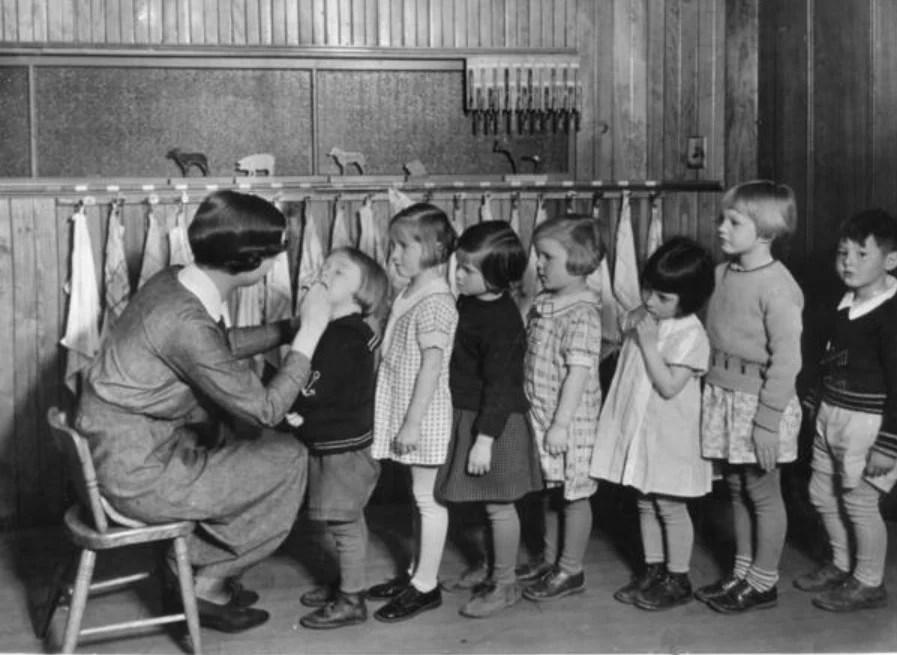 Crianças na fila para um exame de saúde em uma escola, por volta dos anos 40.