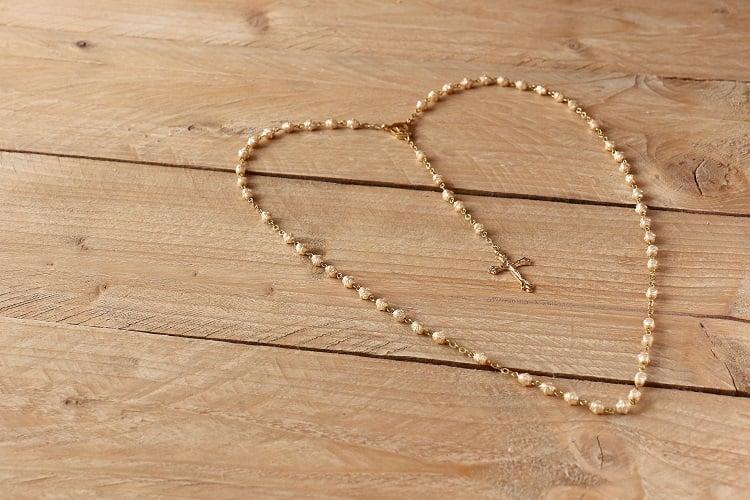 terço em formato de coração em fundo de madeira