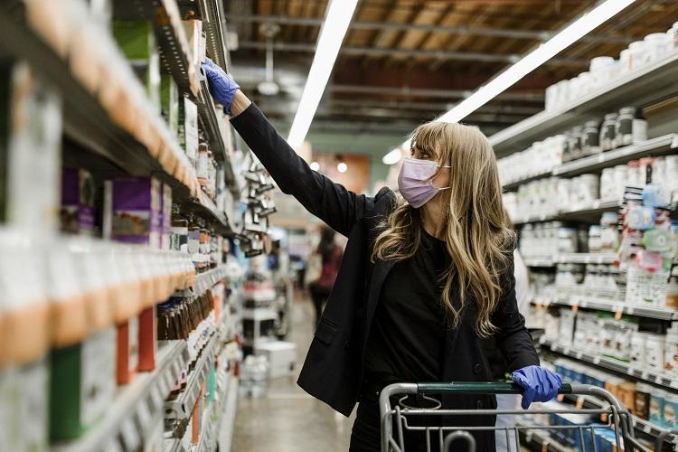 mulher de máscara fazendo compras no supermercado