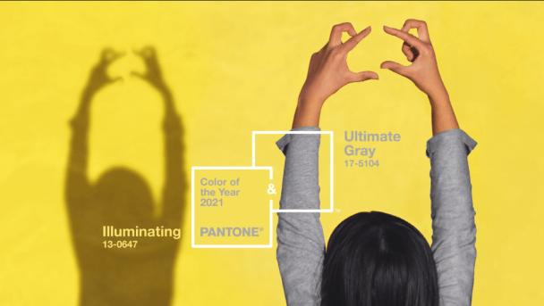 Pessoa com braços para cima usa blusa cinza e olha para parede amarela
