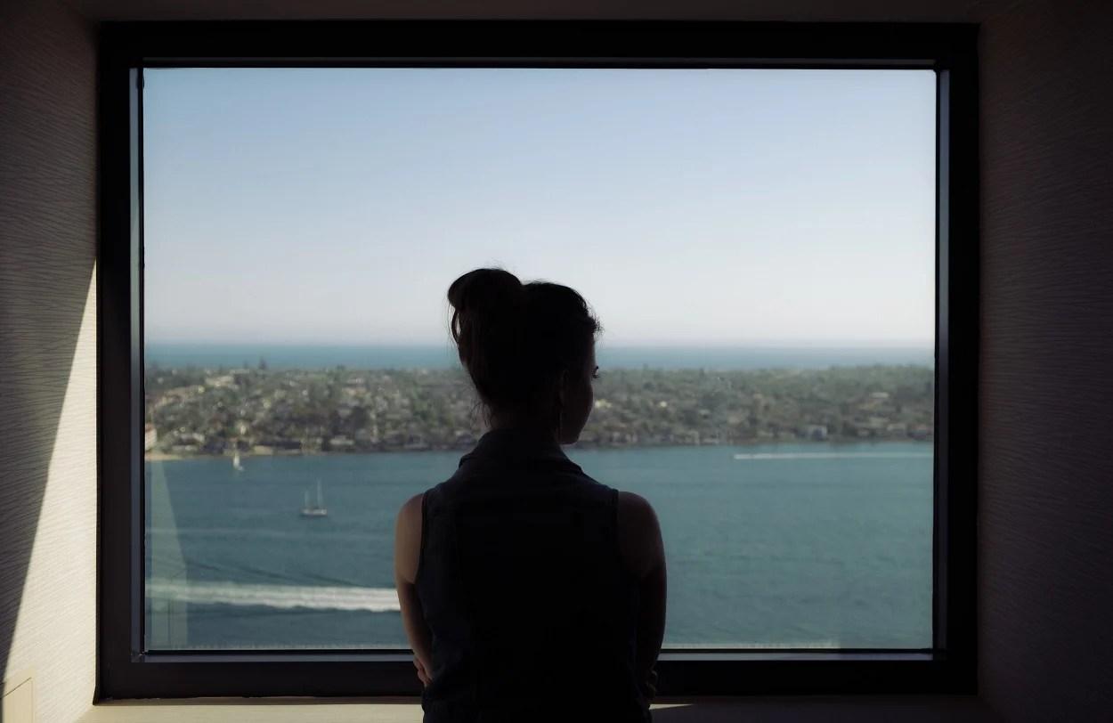 mulher pensativa olhando pela janela