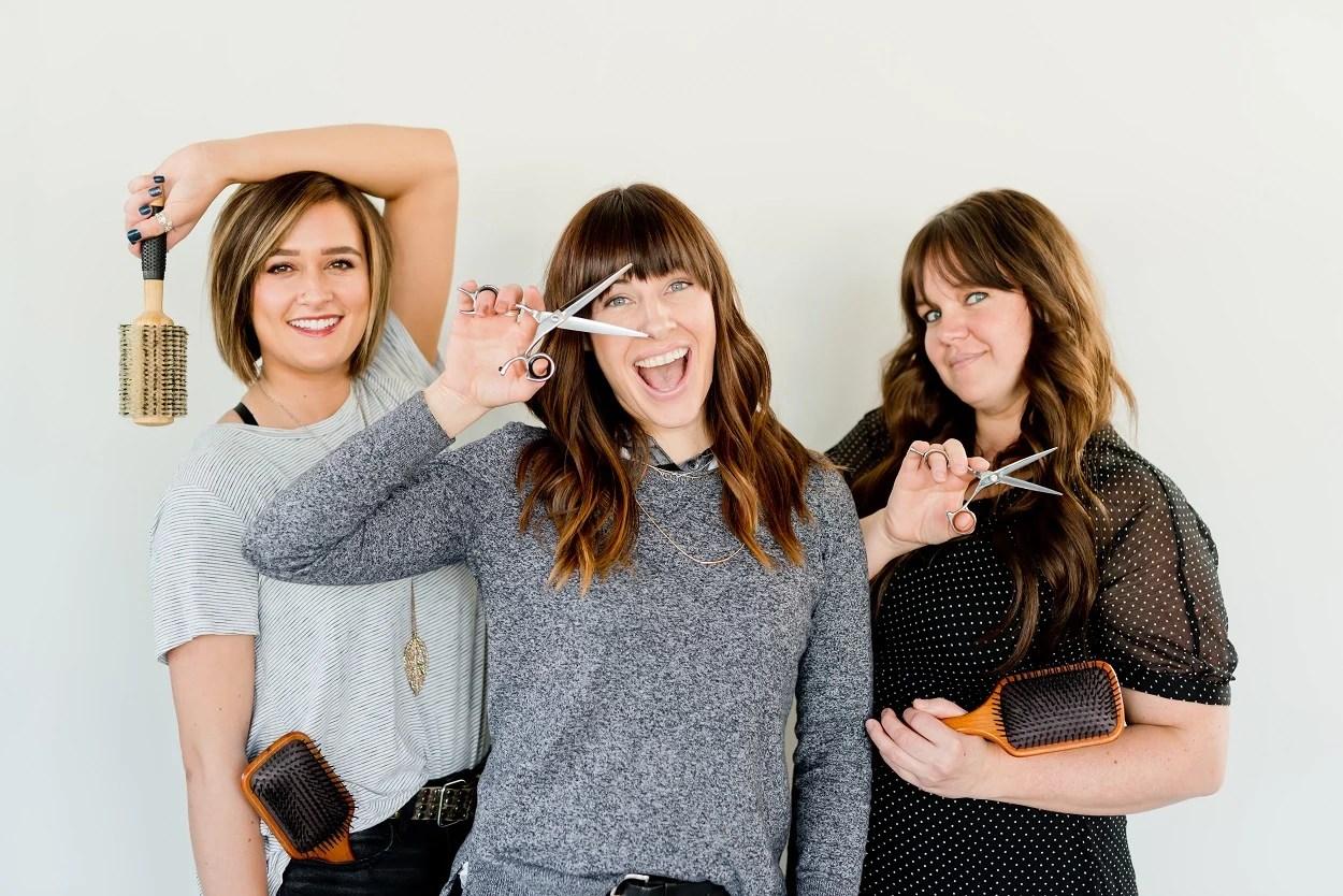 três cabeleireiras posando com tesouras e escovas de cabelo