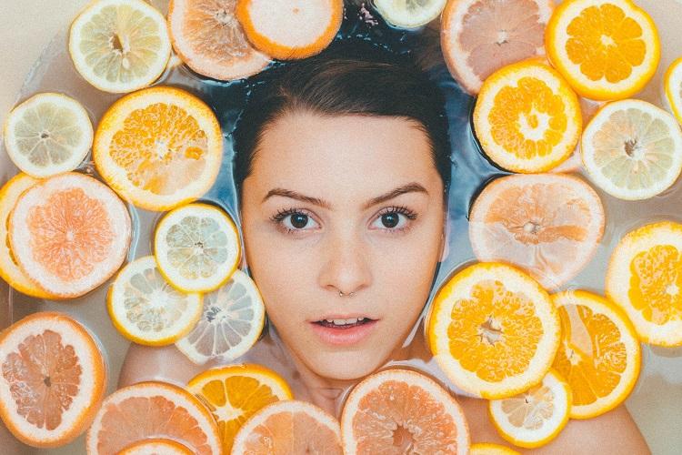 mulher mergulhada em banheira com fatias de laranja e limão