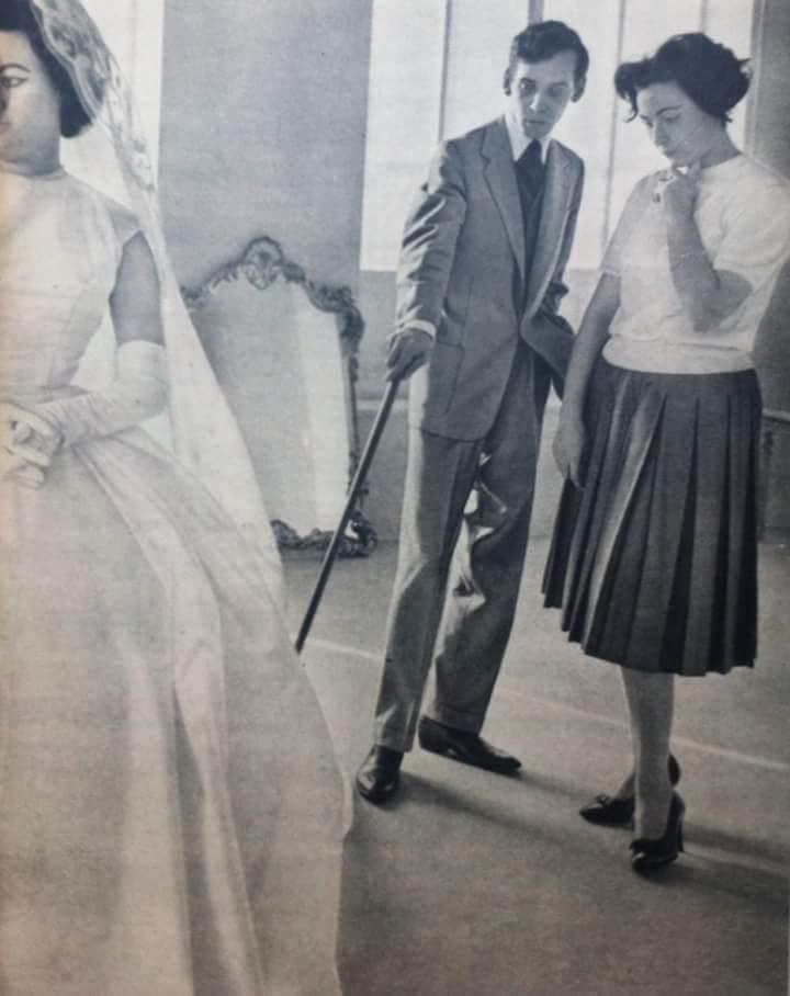 Dener Pamplona jovem a avaliar uma modelo com um vestido de noiva branco.