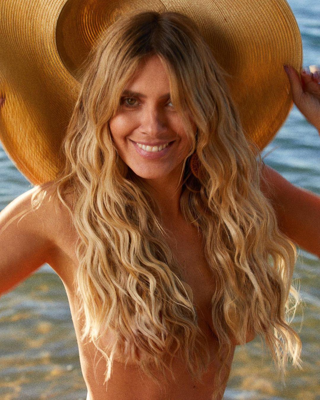 Carolina Dieckmann posa sem parte de cima na praia.