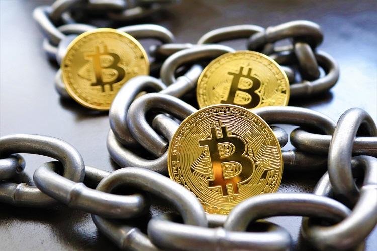 corrente enrolada em volta de moedas BitCoin