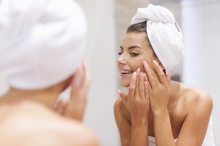 mulher feliz olhando no espelho com espinha curada